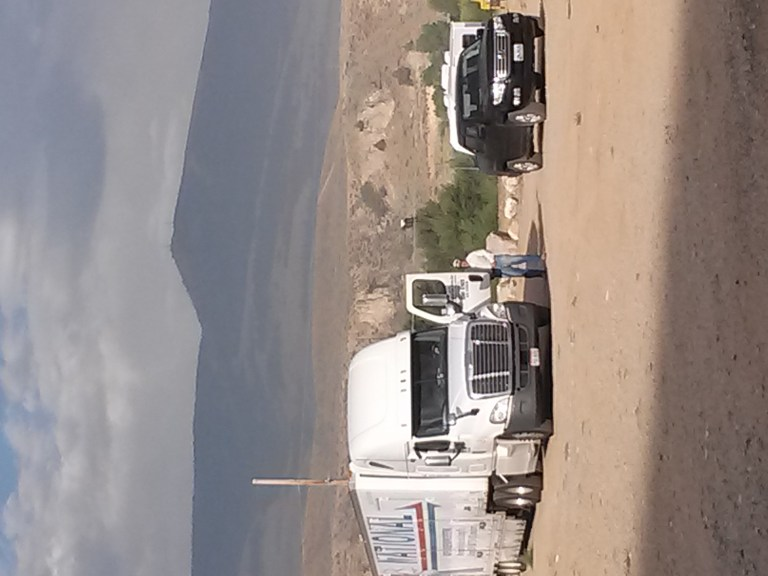 moving truck in front of a mountain and cliff